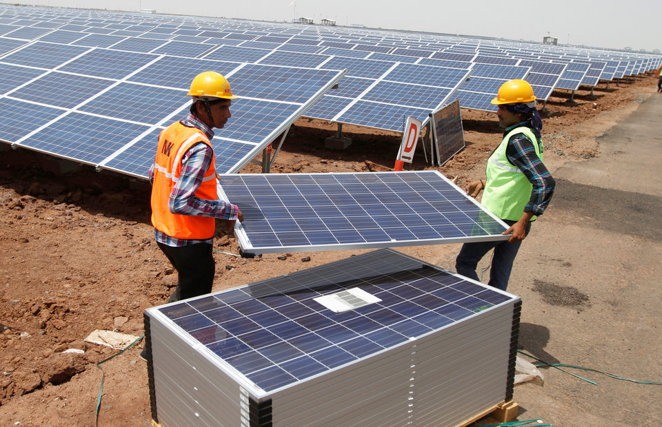 FILE PHOTO: Workers carry photovoltaic solar panels for installation at the Gujarat solar park under construction in Charanka village in Patan district of the western Indian state of Gujarat, April 14, 2012. REUTERS/Amit Dave/File Photo
